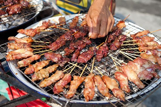 Thai street vendor barbequing satay sticks