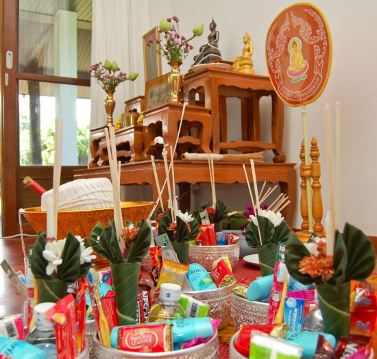 Gifts for monks in front of a Buddha image entwined with holy thread