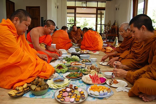 Thai monks eating together at a house blessing