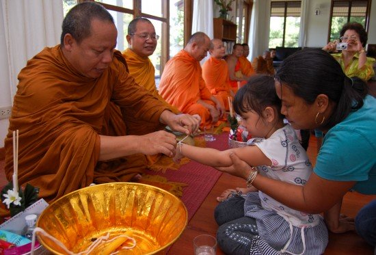 A Thai monk ties white thread around the wrist as blessing
